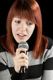 Girl singing karaoke. Girl holding a microphone singing karaoke. Redhead Stock Photo