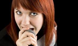 Girl singing karaoke on microphone. Happy redhead girl singing karaoke on a microphone Royalty Free Stock Photo