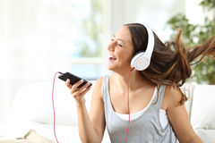 Girl singing and listening music on a couch Stock Images