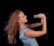 Girl singing in microphone. Whith pleasure Royalty Free Stock Photography