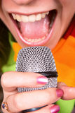 Girl singing in microphone Royalty Free Stock Images