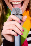 Girl singing in microphone Stock Photography