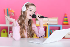The girl  singing into a microphone Royalty Free Stock Images