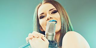 Girl singing into a microphone. Stock Images