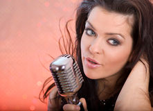 Girl singing in retro mic Stock Images