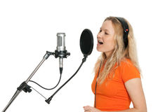 Girl singing with studio microphone. Female singer in orange t-shirt singing with studio microphone. Isolated on white background stock images