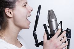 The girl is singing into the studio microphone. Recording the vocals of a young singer. stock photos
