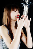 Girl singing to the microphone in a studio Royalty Free Stock Photos