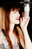 Girl singing to the microphone in a studio. Face and microphone close-up - Young artist woman recording in a studio Royalty Free Stock Image
