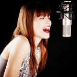 Girl singing to the microphone in a studio Royalty Free Stock Photography