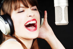 Girl singing to the microphone in a studio Royalty Free Stock Images