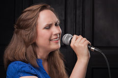 Girl singing to the microphone in a studio. Studio shooting on a dark gray background Stock Images