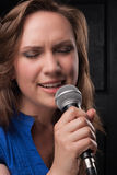 Girl singing to the microphone in a studio. Studio shooting on a dark gray background Stock Image