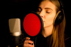 Girl singing to microphone in studio. Process of creating new song Royalty Free Stock Photography
