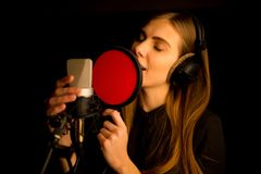 Girl singing to microphone in studio. Process of creating new song Royalty Free Stock Photos