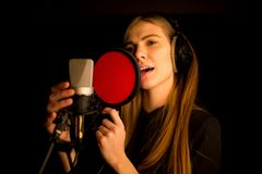 Girl singing to microphone in studio. Process of creating new song Stock Images
