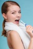 Girl singing using toothbrush. Stock Photo