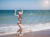 A girl sings a merry dance in the sun by the sea. royalty free stock image