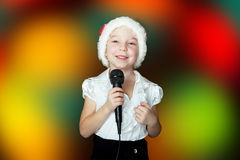 A girl sings a song in a cap of Santa Claus Royalty Free Stock Photo