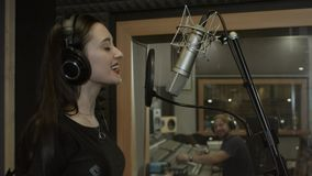 Girl sings well in the studio.