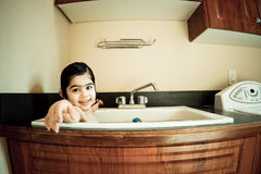 Girl in the sink. This child is having bath in a normal washbasin Royalty Free Stock Photography