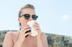 Girl sipping coffee from takeaway cup outside Stock Photos