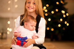 Girl and sister baby at Christmas Stock Photography
