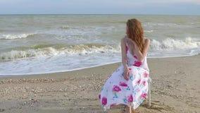 Girl sit on beach in dress. stock video