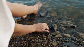 Girl sit on beach and toutch rocks. Girl on beach rocks and stones sea stock video