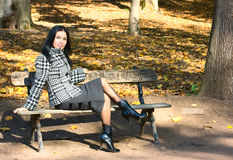 Girl sit on bench. In fall park Royalty Free Stock Photography