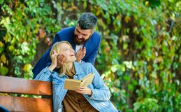 Girl sit bench read book while wait boyfriend. Wait him for date. Dating in park. Romantic relations concept. Park best. Place for romantic date. Couple in love stock photography