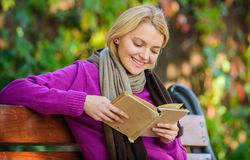 Girl sit bench relaxing with book fall nature background. Intellectual hobby. Lady bookworm read book outdoors fall day. Woman reading book. Fall literature stock image
