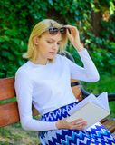 Girl sit bench relaxing with book, green nature background. Reading literature as hobby. Girl keen on book keep reading. Woman blonde take break relaxing in stock photography