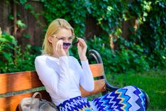 Girl sit bench relaxing in shadow, green nature background. Woman blonde with sunglasses dream about vacation, take stock photo