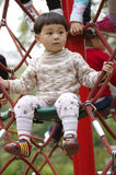 Girl sit on cable ladder. A chinese girl cliambing the ropeladder Royalty Free Stock Photos