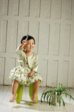 The girl sit on the chair. The NO.1 girl sit on the chair and the orchid beside her Stock Photo