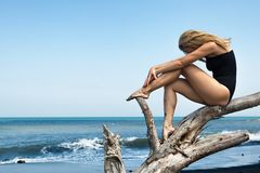 Girl sit on dead tree branch on black beach. Girl with slim body in swimsuit sit and relax on old tree snag, posing on black sand sea beach. Young dreaming woman stock photography