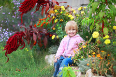 Girl sit in flowers in the park. Royalty Free Stock Photo