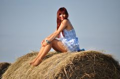 Girl sit on haystack Royalty Free Stock Images
