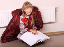 Girl sit near radiator with book. Stock Image