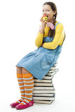 Girl sit on pile of books and eat apple Royalty Free Stock Photos