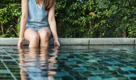 Girl sit on pool edge. In relax emotion with green plant background Royalty Free Stock Photos
