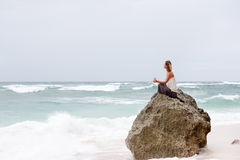 Girl sit at the seaside on the rock and meditating in yoga pose Stock Photo