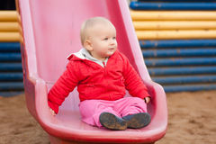 Girl sit on side after slide down Stock Photo
