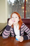Girl sit at table in cafe and eats ice cream Stock Images