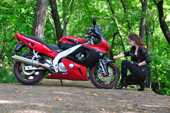 The girl sit and talk with sports bike in the woods Royalty Free Stock Photos