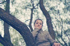 Girl sit on the tree Stock Images
