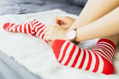 The girl sit on a white carpet and put on socks, white punctuate red side. Royalty Free Stock Images