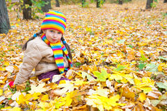 Girl sit on yellow leaves in autumn park Royalty Free Stock Photo