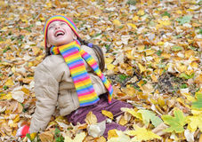 Girl sit on yellow leaves in autumn park Royalty Free Stock Images